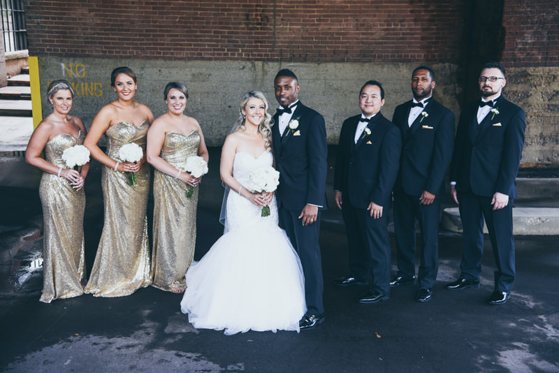 bride and groom with bridal party in gold taking photos in a loading dock