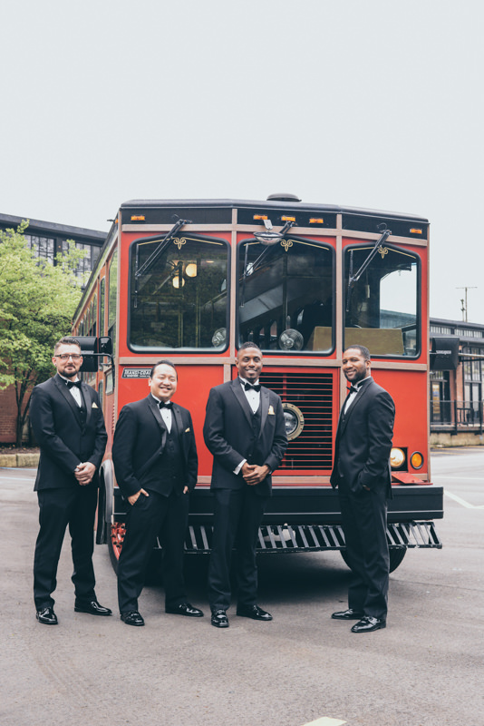 Groom and groomsmen in front of an historic red trolley