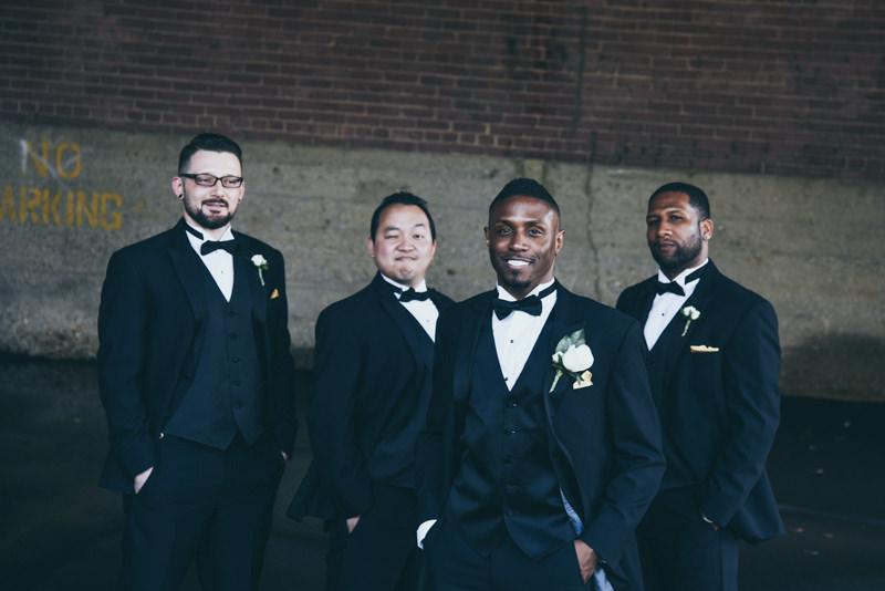 groom and groomsmen in black tuxedos near loading dock