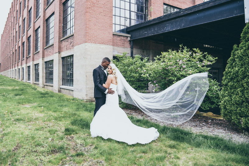 bride and groom in front of industrial loft building with long veil blowing in the air