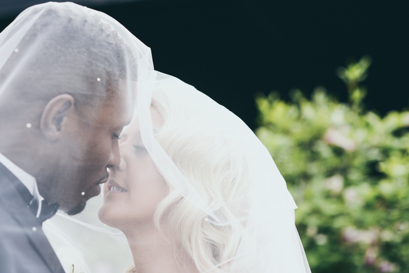 groom leaning in for a kiss beneath a veil