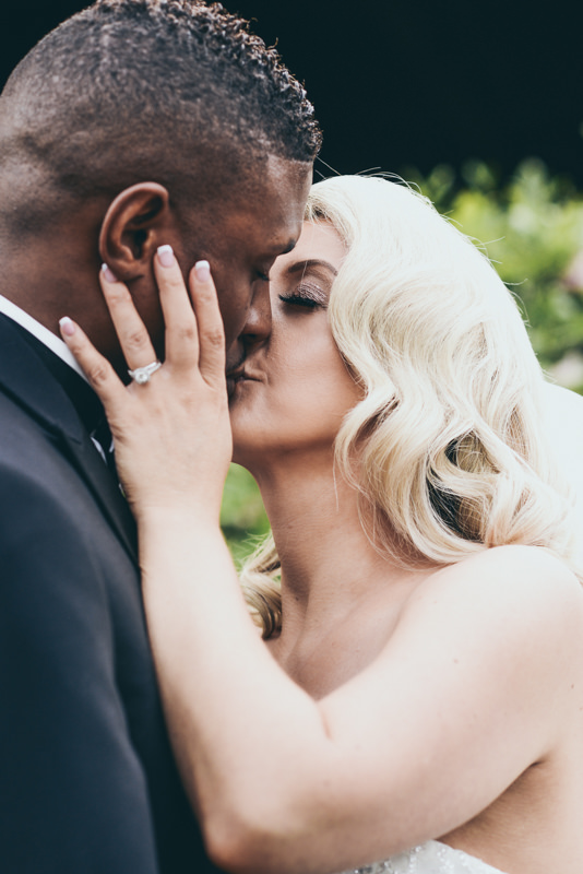 bride holding groom's face as she kisses him