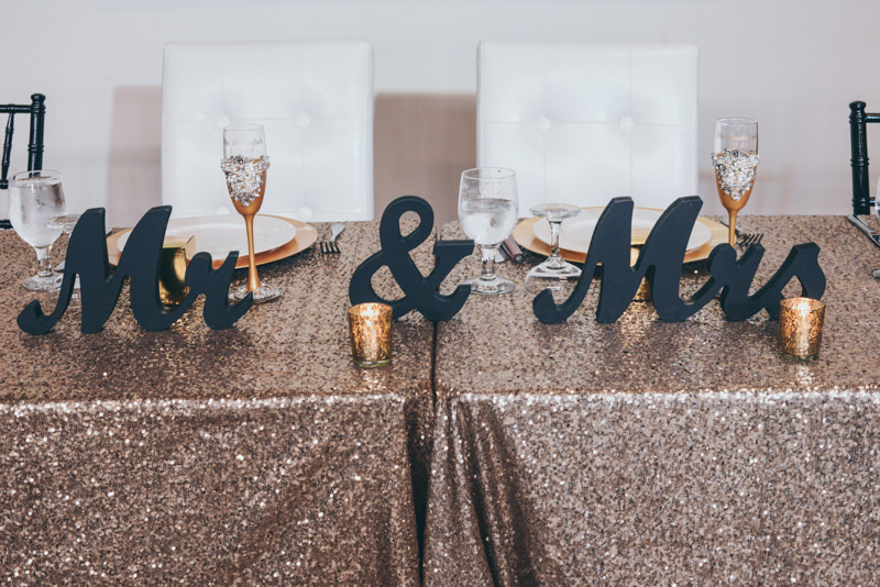 Mr and Mrs signs with golden accent items on sequined tablecloth at head table