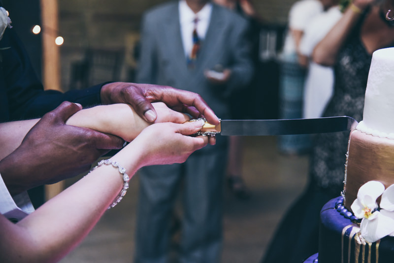 close up of bride and groom's hands while they cut their cake
