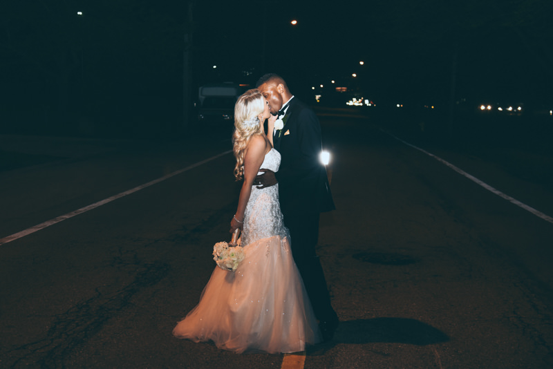 backlit photo of bride and groom on a city street
