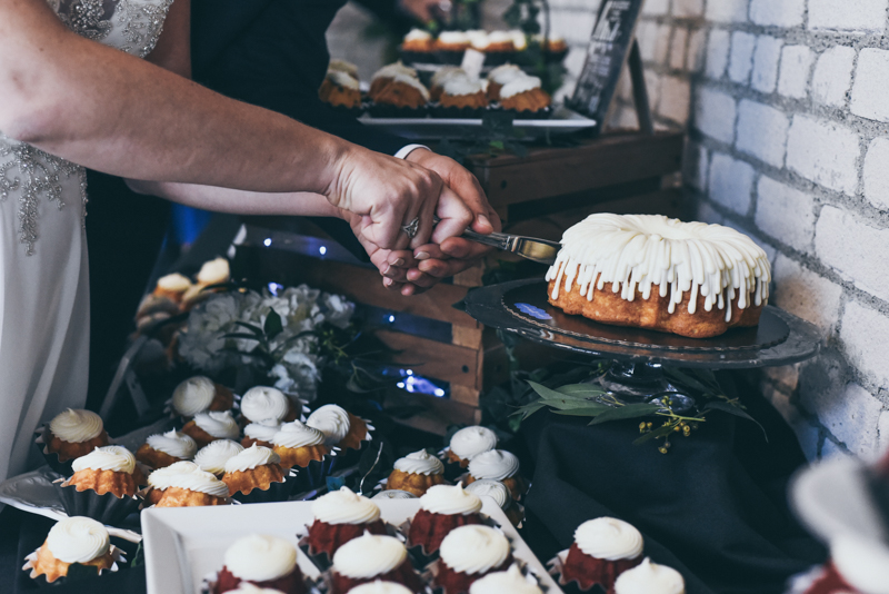 close up of bride and grooms hands cutting a bundt cake