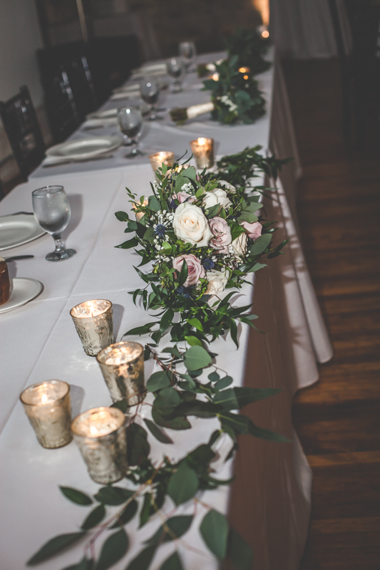 wedding bouquet of pink, ivory and lavender roses at a wedding reception