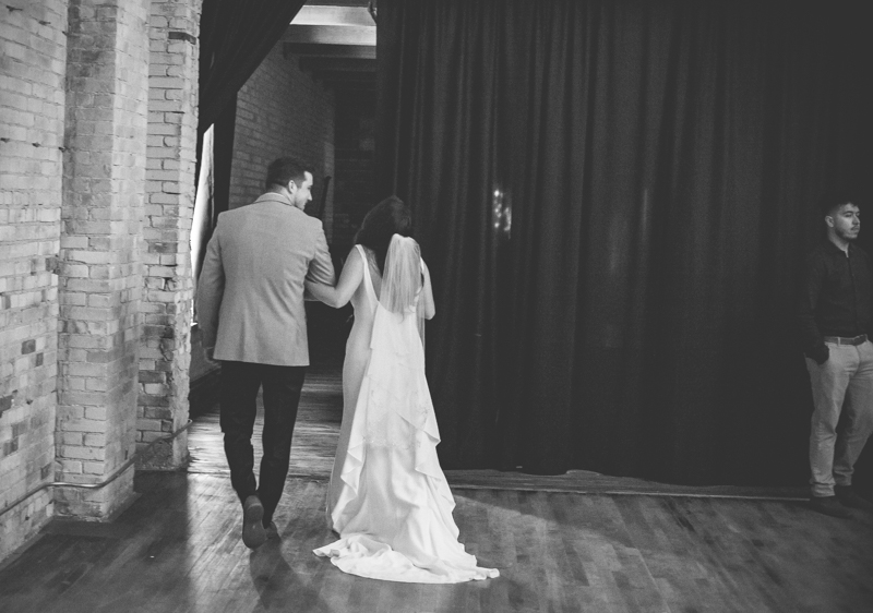 bride and groom walking behind a curtain after their wedding ceremony