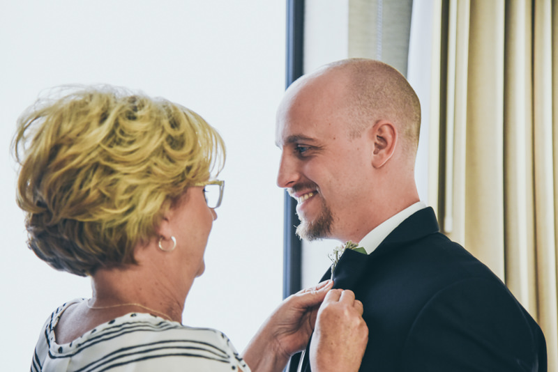 Groom's Mother putting the flower on his jacket