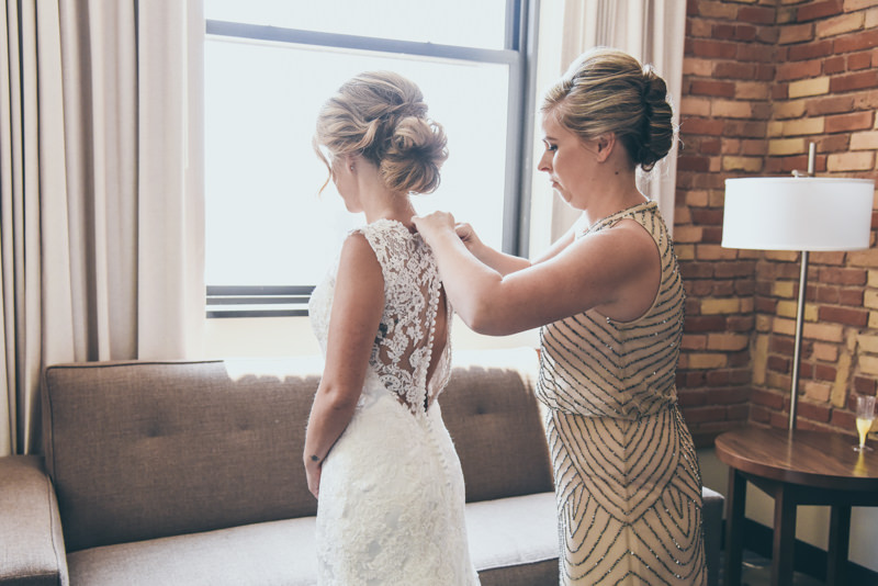 the mother of the bride in a champagne dress fastening her daughters wedding gown