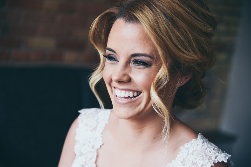 image of a smiling bride as she looks out the window