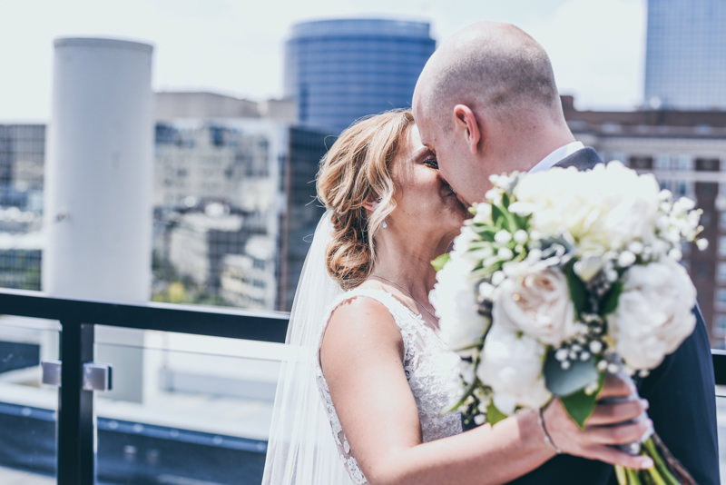 bride and groom kissing on the roof of a city building