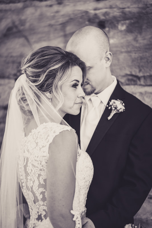 black and white image of a groom leaning into his bride in front of a stone wall