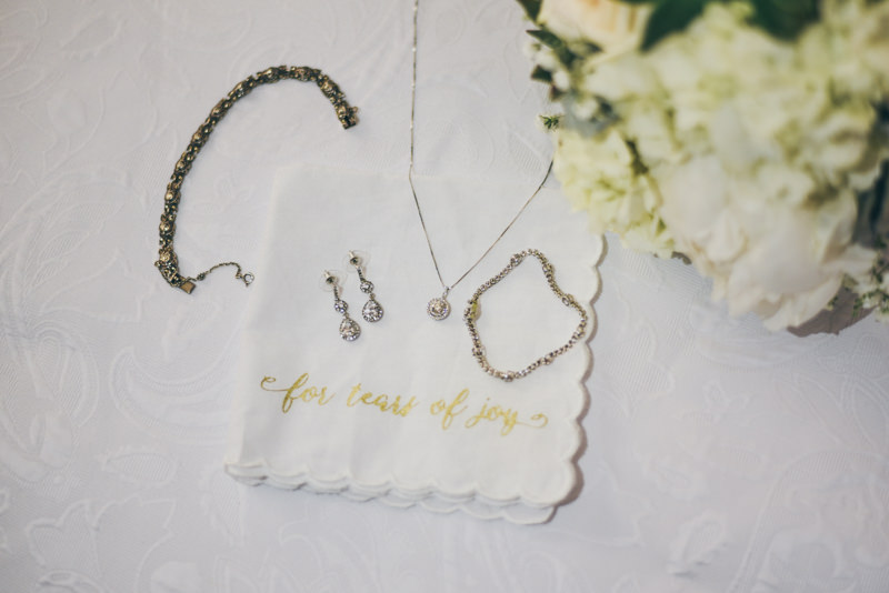 bridal jewelry and handkerchief with bouquet on white background