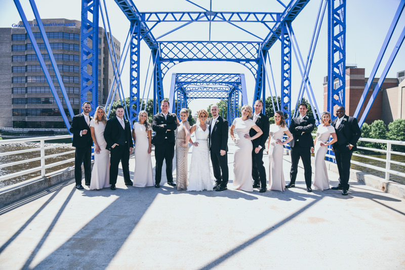 bridal party laughing on a blue bridge