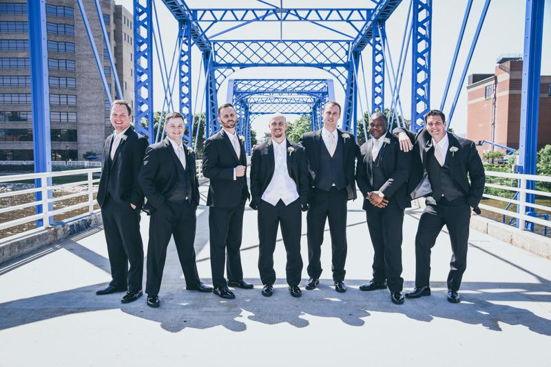 groom and groomsmen in black tuxes on a blue bridge