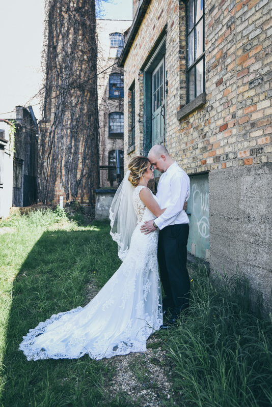 bride and groom facing each other on green grass in front of an old brick warehouse
