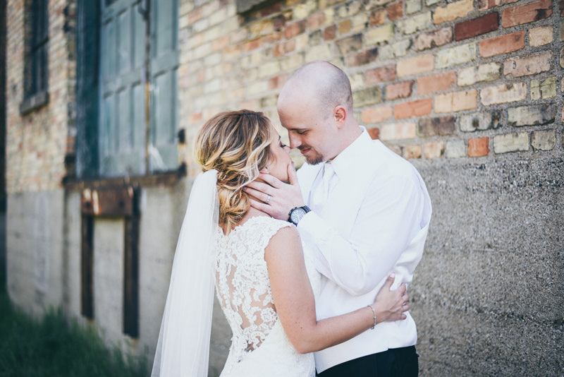 groom tenderly holding his brides face as he leans in for a kiss in front of an old brick building