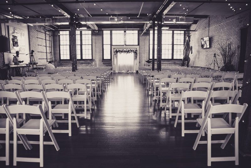 black and white image of a wedding venue before the ceremony with bistro lights and white chairs