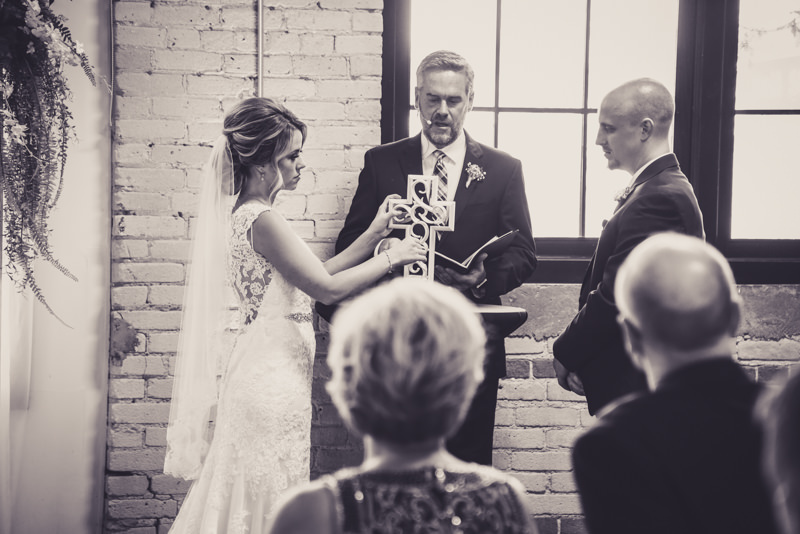bride and groom building a cross during wedding ceremony