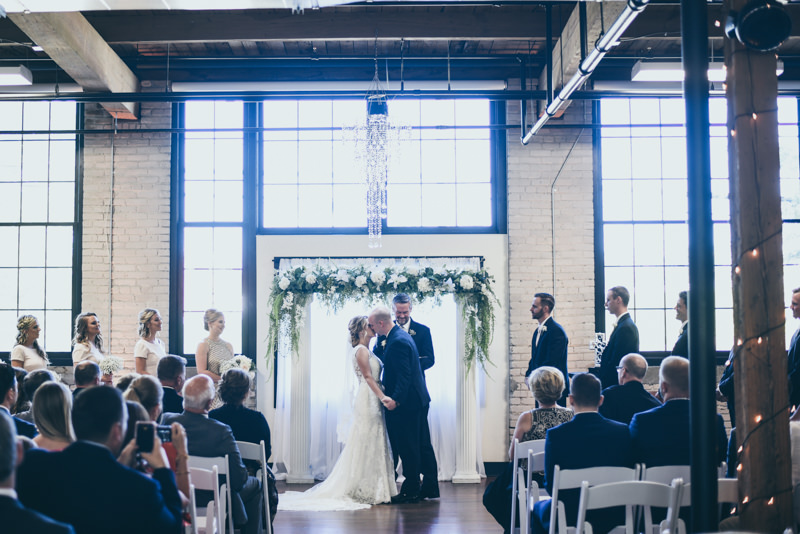 first kiss between bride and groom at wedding ceremony