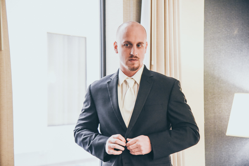 groom getting ready in a hotel room in front of a large window