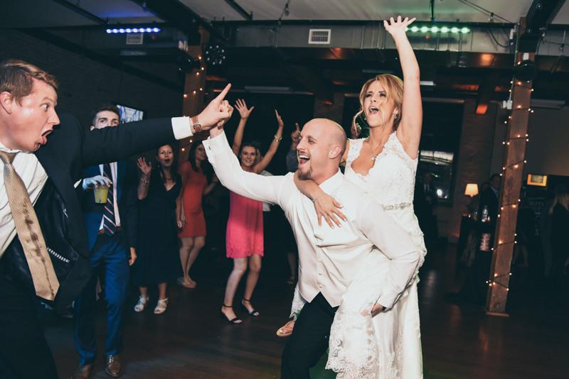 bride and groom having fun dancing at wedding reception