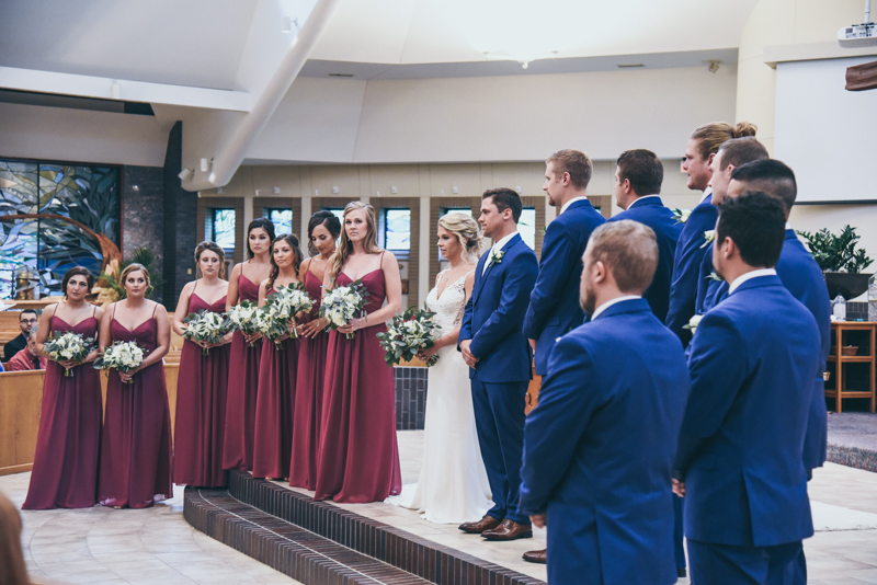 bride and groom standing with bridal party during wedding ceremony