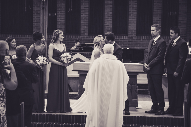 bride and grooms first kiss during their wedding ceremony