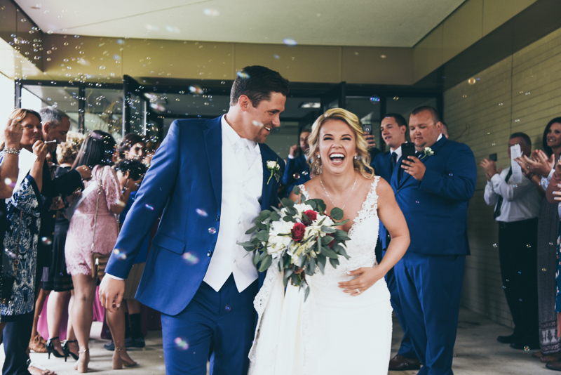 bride and groom laughing as they depart their wedding ceremony as guests throw confetti