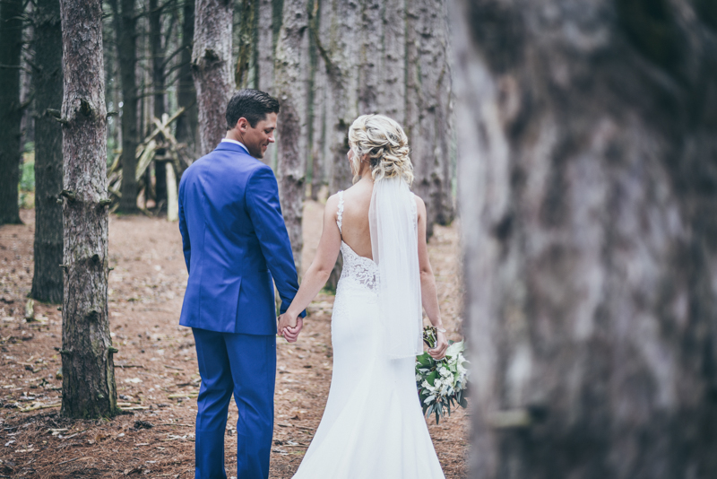 bride and groom walking away looking at each other in a pine forest