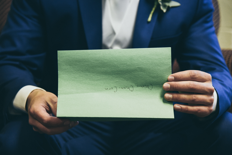 close up of grooms hands holding a letter from his bride