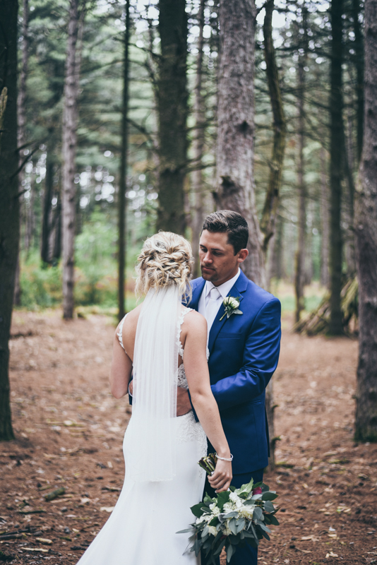 groom holding his bride close in a pine forest