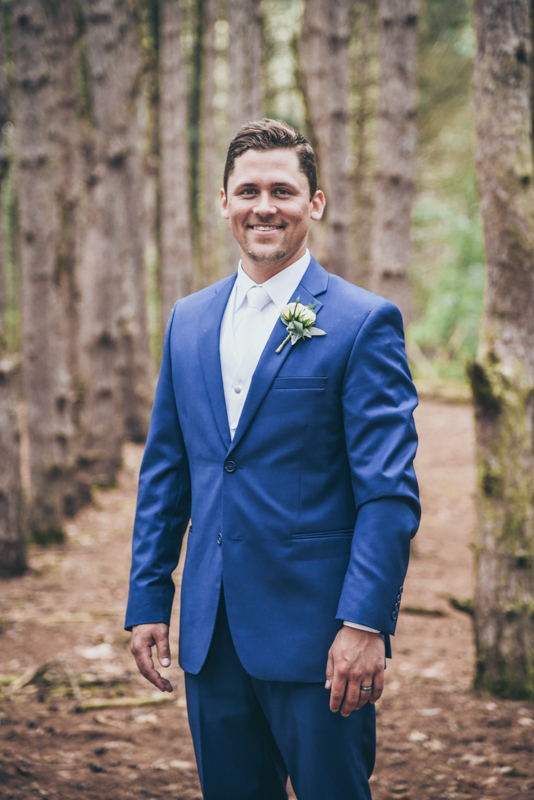 image of a groom in navy in a pine forest