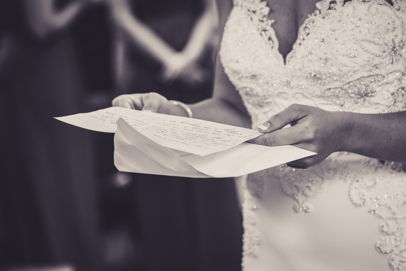 close up of a brides hands holding a letter from her groom