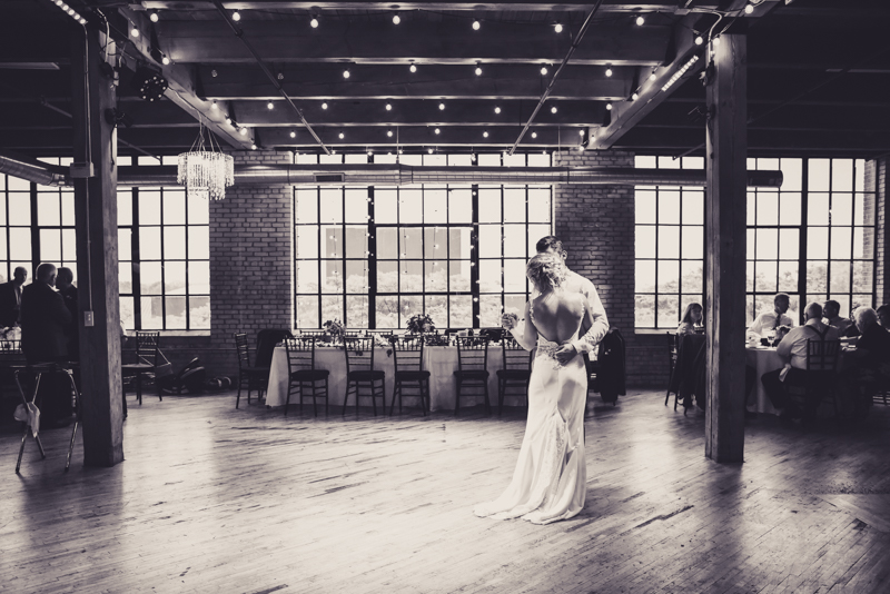 black and white image of bride and groom taking first dance