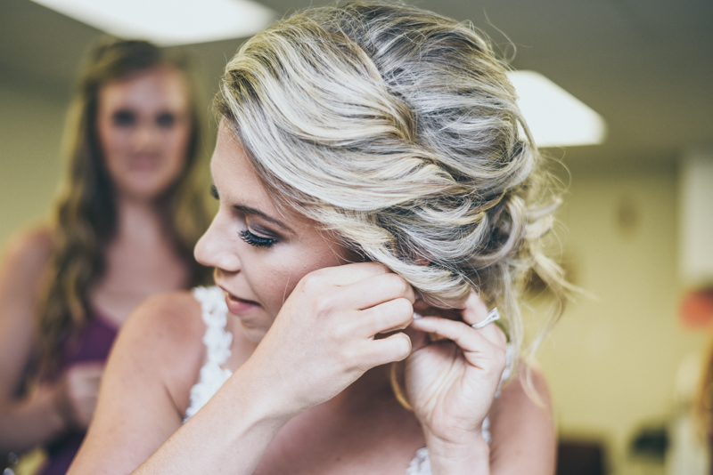 photo of a bride putting her earrings on while a bridesmaid watches