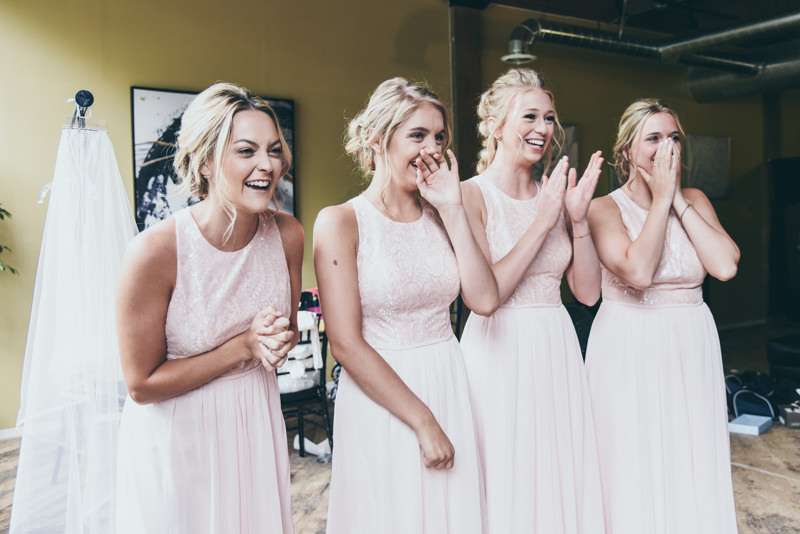 bridesmaids excitement at seeing the bride in her dress for the first time