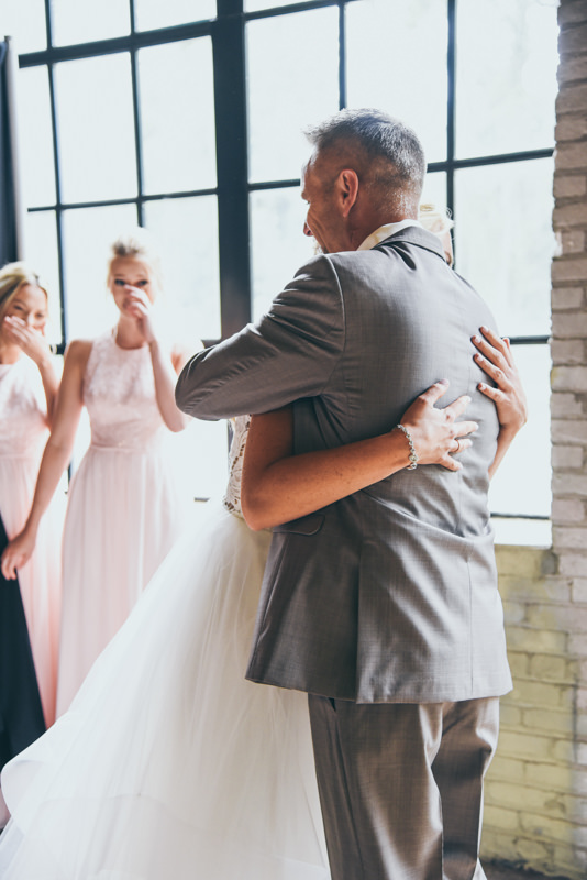 father holding his daughter close when he sees her for the first time in her wedding dress