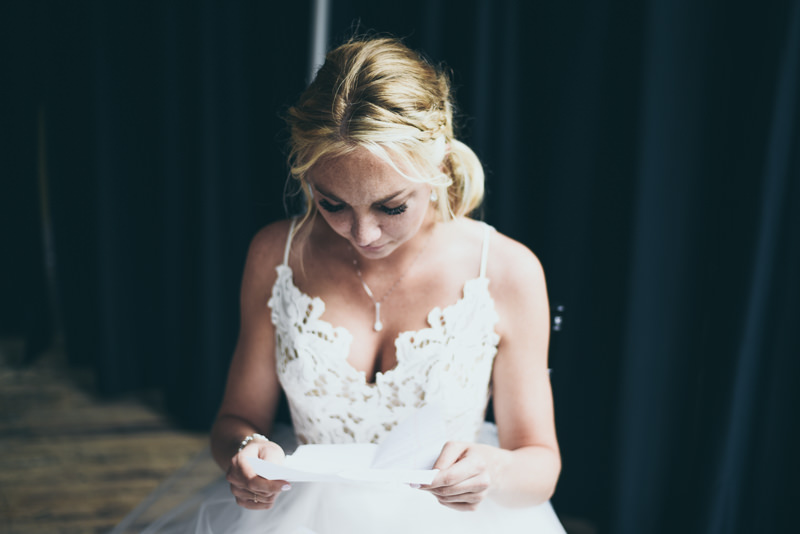 bride reading a letter from the groom before the ceremony