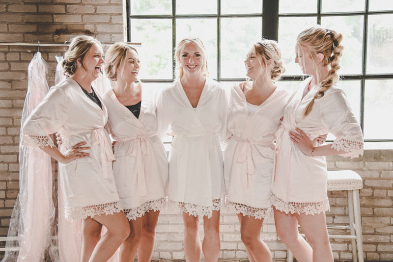 bride and bridesmaids in robes laughing