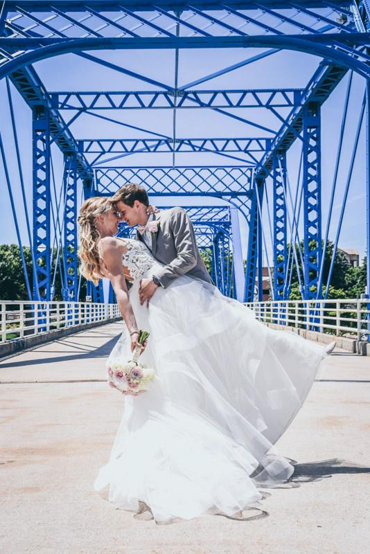 groom dipping his bride on a blue bridge