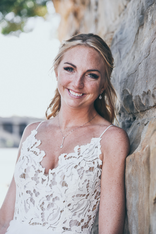 a smiling bride leaning against a stone wall