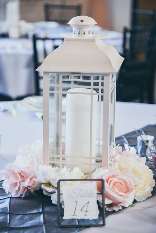 white lantern with fresh flowers on a gray table runner