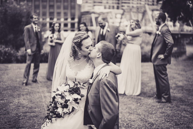 black and white image of bride and groom kissing while bridal party stands behind them