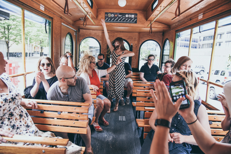 a group dancing and having fun on an open air trolley