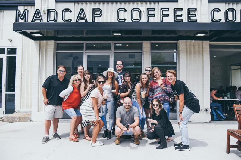 team photo outside a downtown coffee shop
