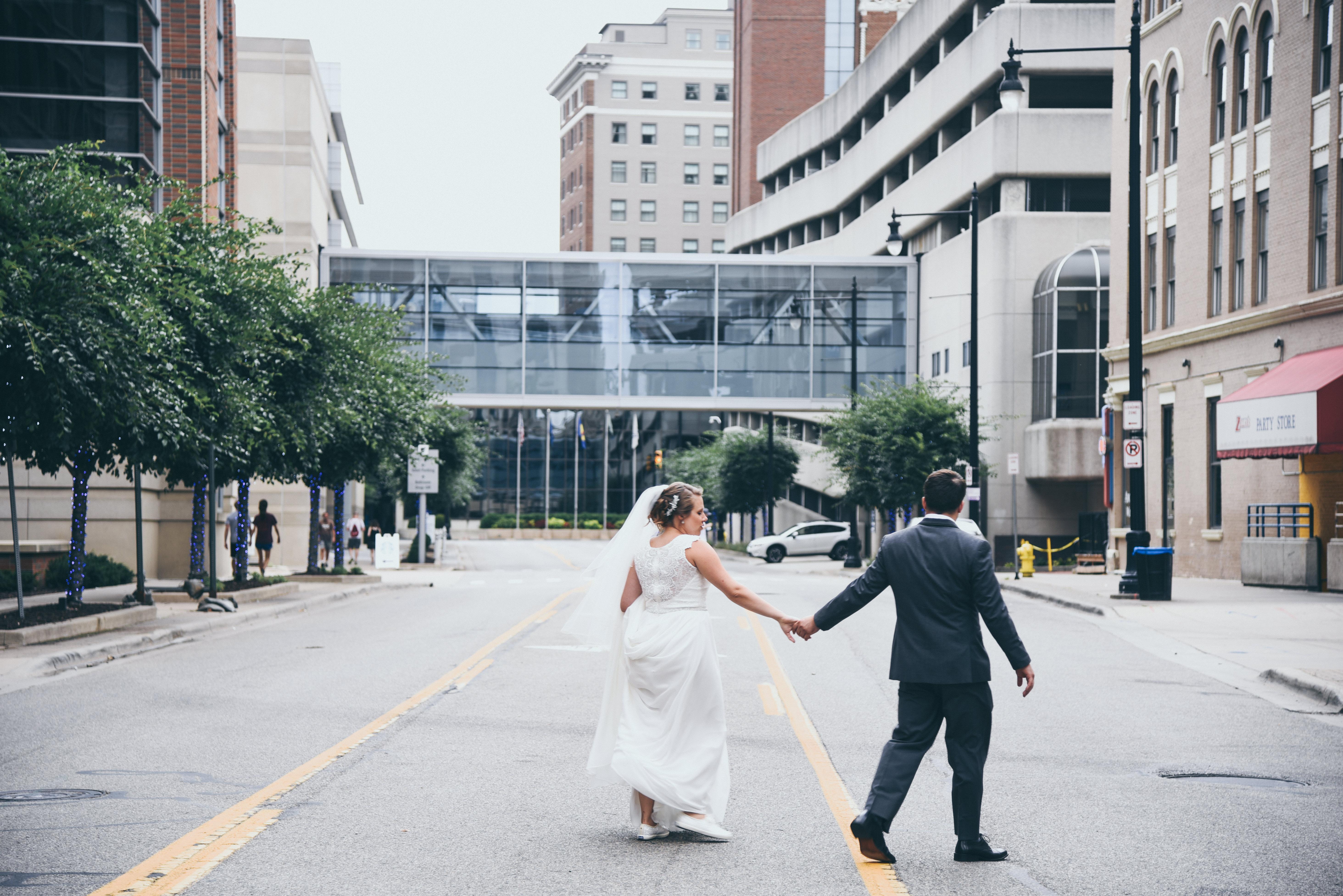 bride and groom walking across a city street