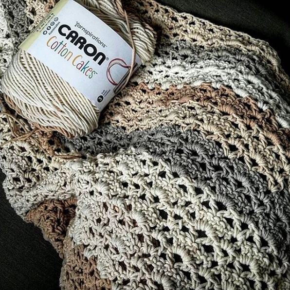 Image of 1 skein of Caron Cotton Cakes in Garden Path on top of the Reverie triangle shawl in progress.