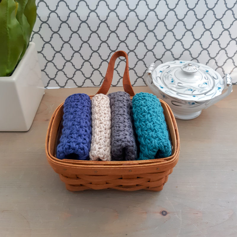 Four Crochet dishcloths in basket with flower accent and ceramic bowl accent